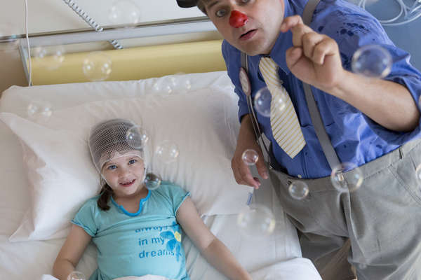 Injured girl in hospital bed smiling about bubbles thrown by a male clown