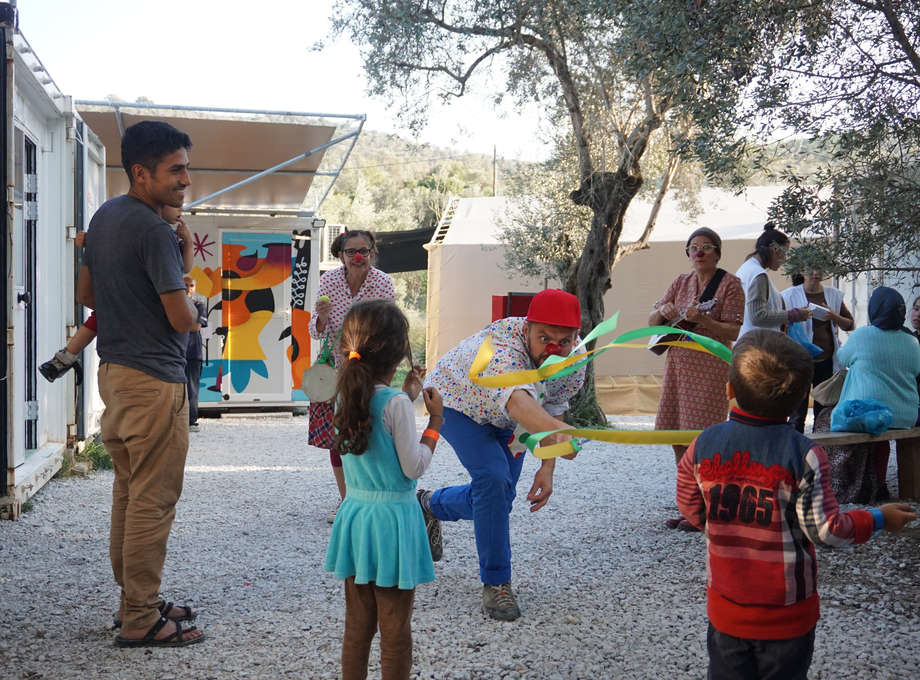 RED NOSES clowns interact with children in the MORIA refugee camp by performing tricks to make them smile