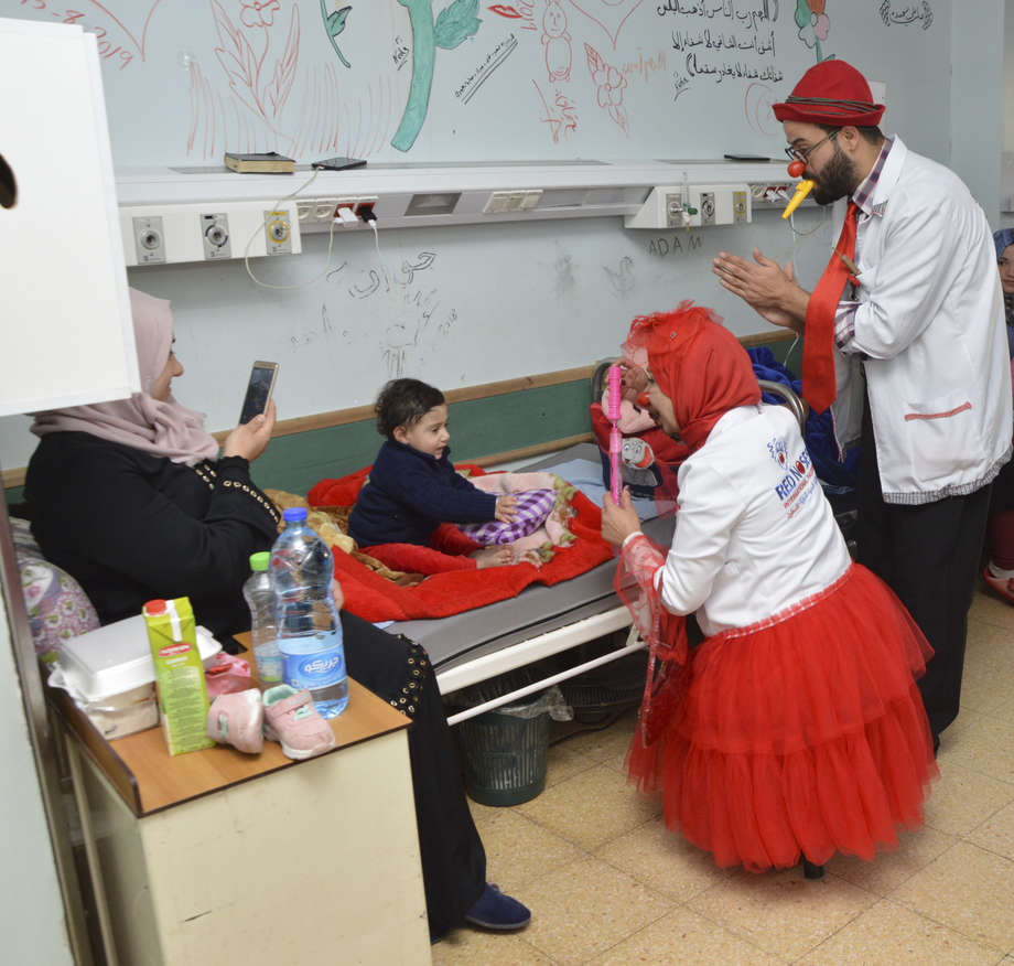 Two RED NOSES clowns, male and female, play with baloons in their hand with a small child on his hospital bed as his mother is taking a picture with her phone. a