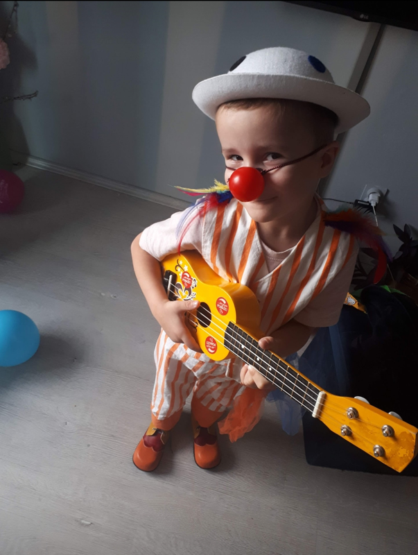 Little Leo wears a red nose, a hat and plays the ukulele in his clown costume.