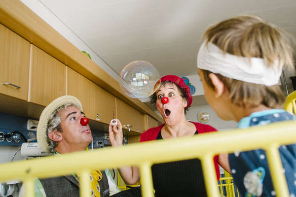 two clowns playing with a bubble in front of hospitalized boy