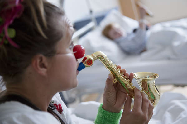 Female clown playing the saxophone to boy in hospital room