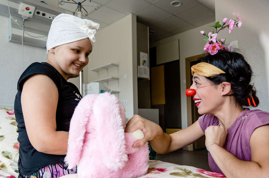 Girl on hospital bed smiling to female clown