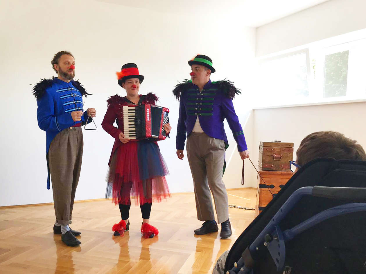Three RED NOSES clowns perform a song in front of the children present in the room.