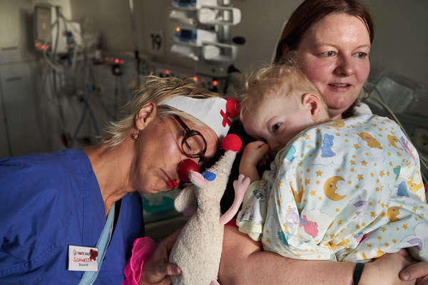 A female clown stands next to a little boy and his mother, encouraging them before the heart surgery