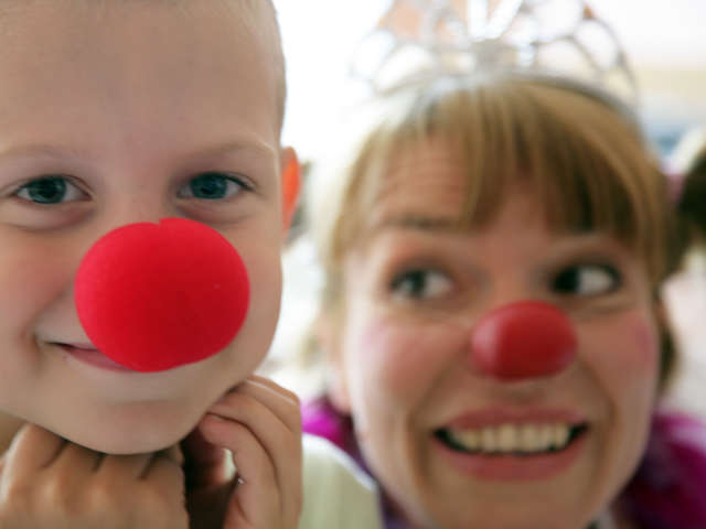 boy with red nose smiling and female clown behind him