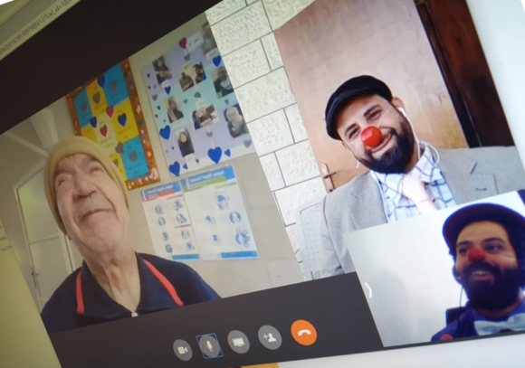 Two male clowns from RED NOSES Palestine smile during an online clowning visit to an elderly man whose face is bright and joyful.