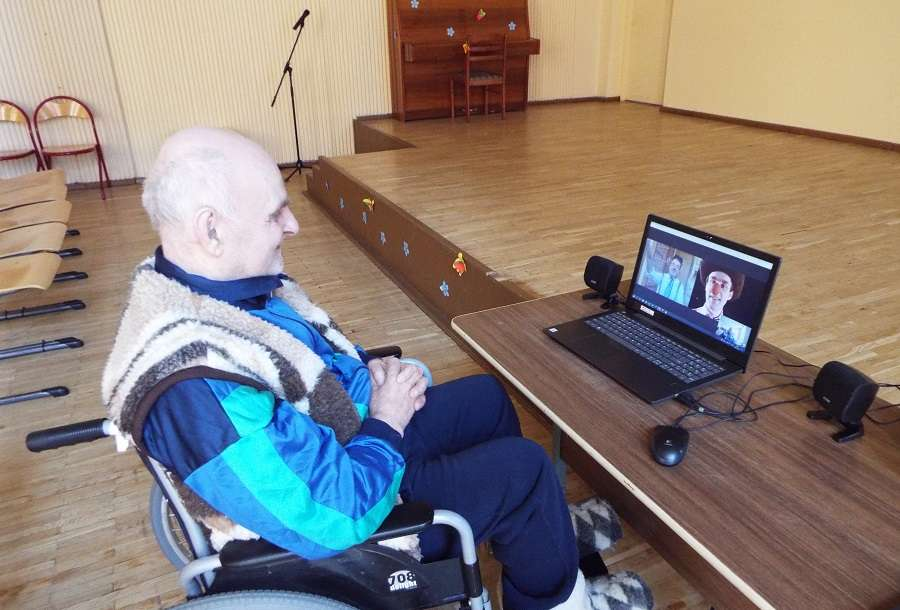 An old man in an elderly care home sits in front of the laptop in a big empty room and watches a clown from RED NOSES Lithuania perform a show online