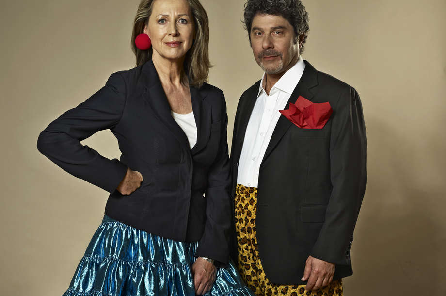 RED NOSES International founders Monica Culen, CEO, and Giora Seeliger, Artistic Director, stand next to each other in colourful outfits.