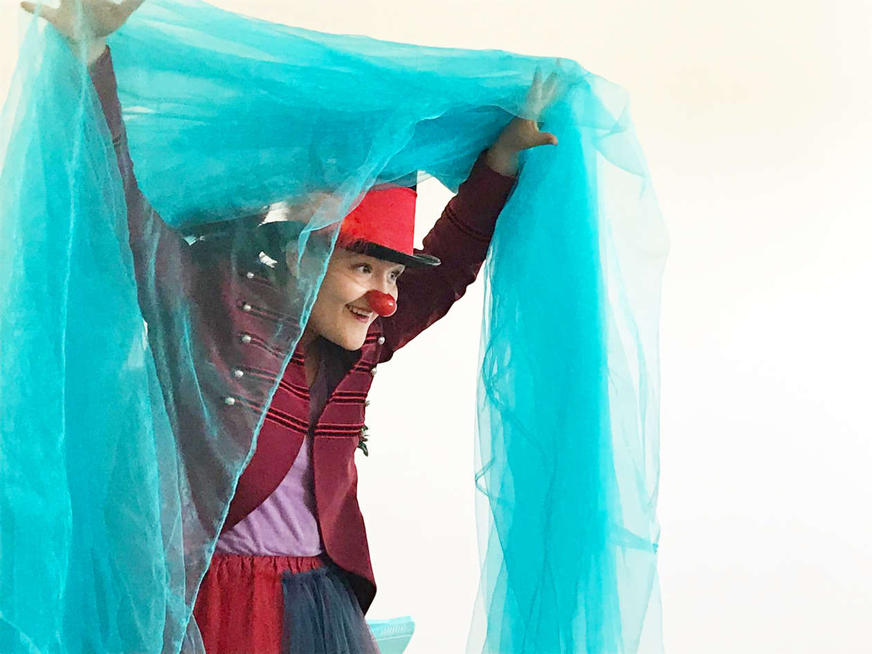 A female clown with a big red hat and a red nose holds a blue, light silk curtain with her hands.
