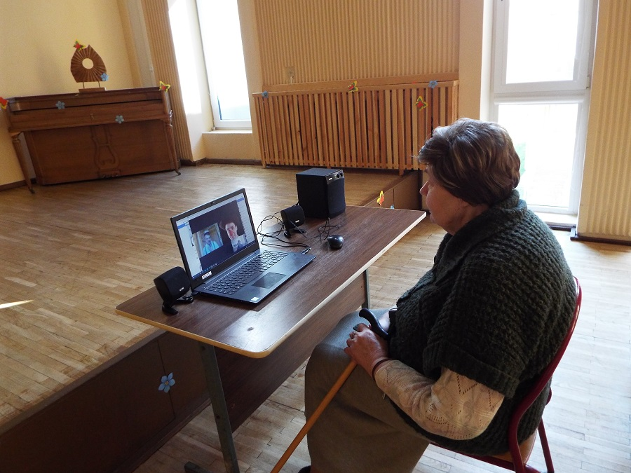 An old woman watches a clown intervention online as she sits in front of a laptop in a big empty hall in her elderly care home in Lithuania